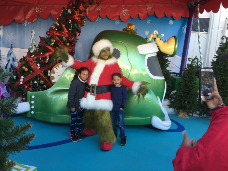 The Grinch posing with two happy kids at Universal Studios Hollywood