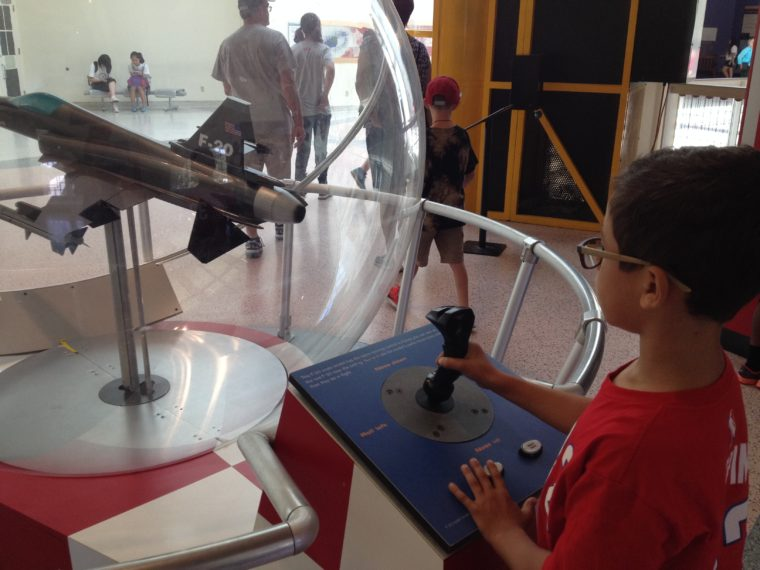 a kid plays with a Hands-on exhibit at the CA science Center