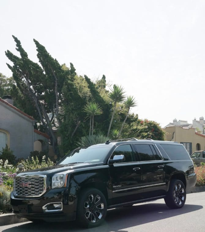 GMC Yukon XL Denali parked in front of a big tree