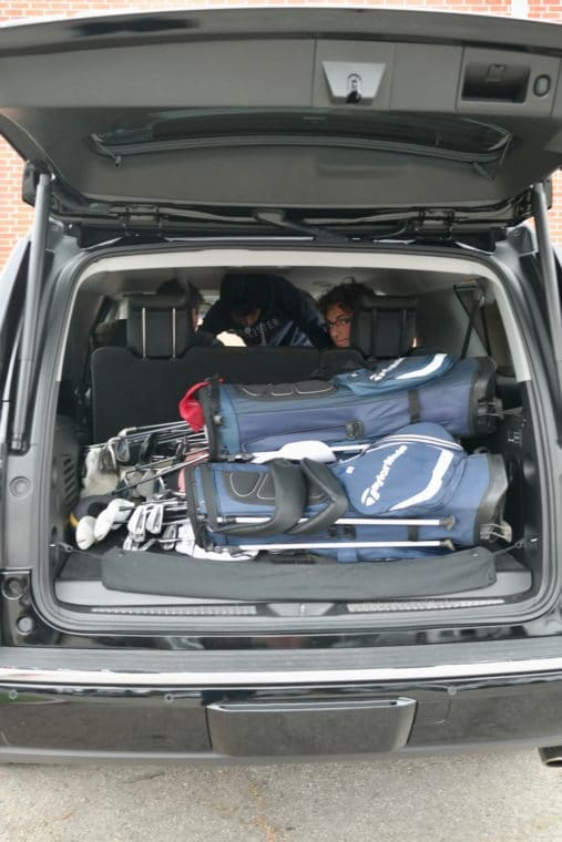 golf clubs stacked in back of GMC Yukon XL Denali