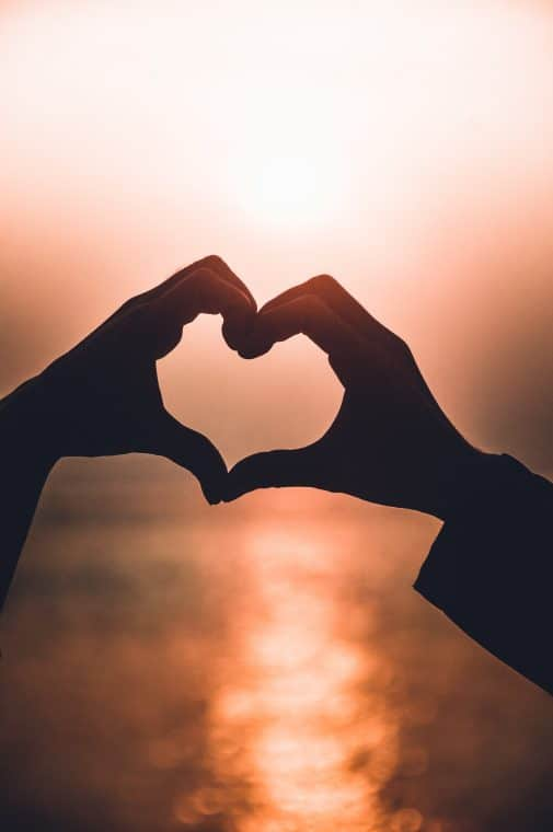 two hands forming heart shape silhouette
