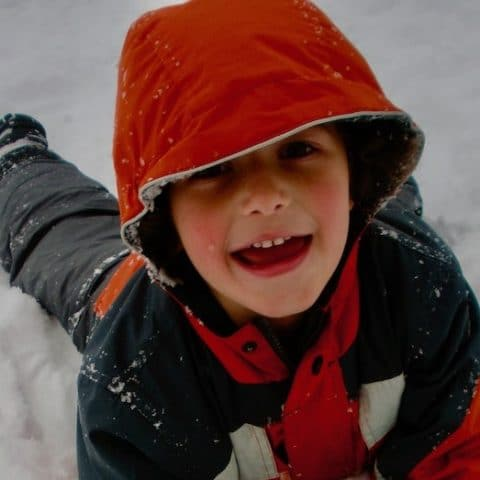 happy kid playing in snow near los angeles featured image