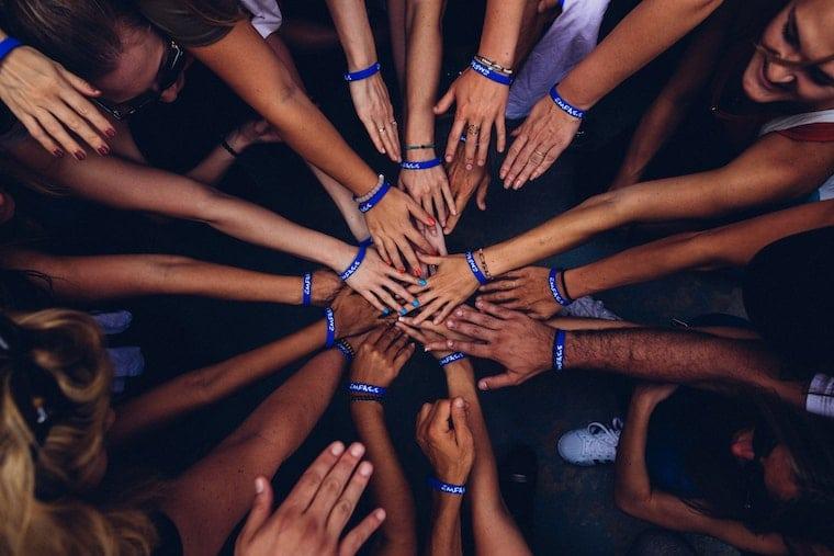 hands in center teamwork volunteer hours