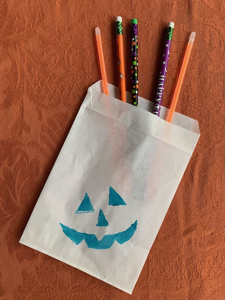 Teal treat bag with pencils and glow sticks for Halloween
