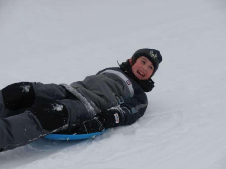 happy kid on pan sled