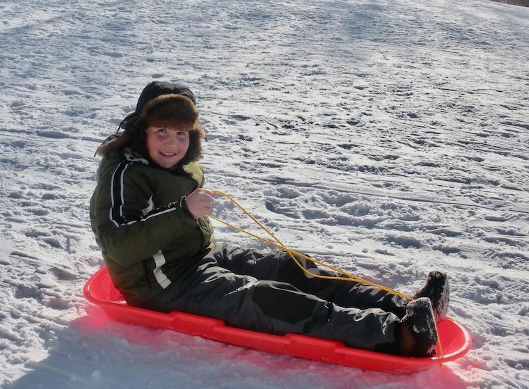 smiling kid on sled