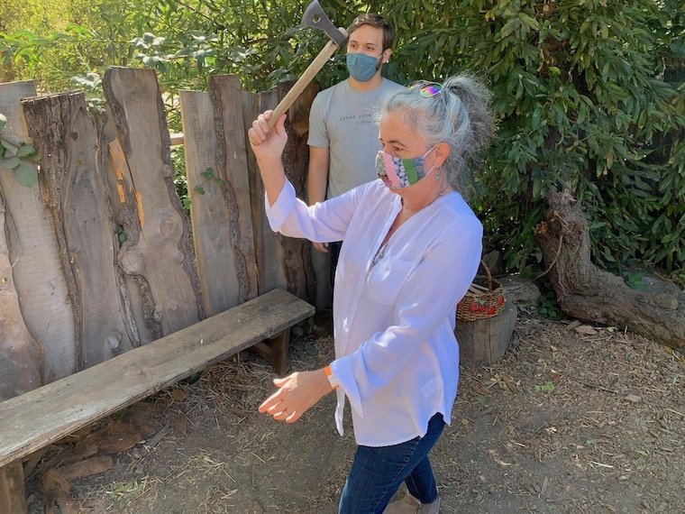 MomsLA Founder Sarah Auerswald throwing a tomahawk with a patient Stone Soup Farm staff member watching