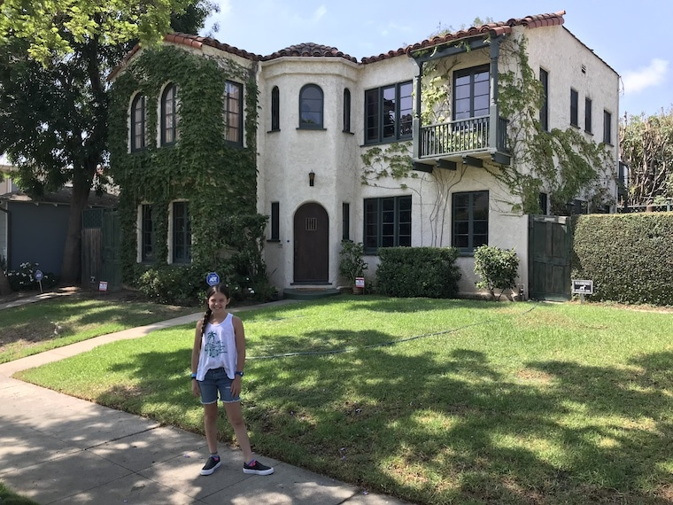 "Mitch and Cam's TV house from ""Modern Family,"" with young girl standing in front"