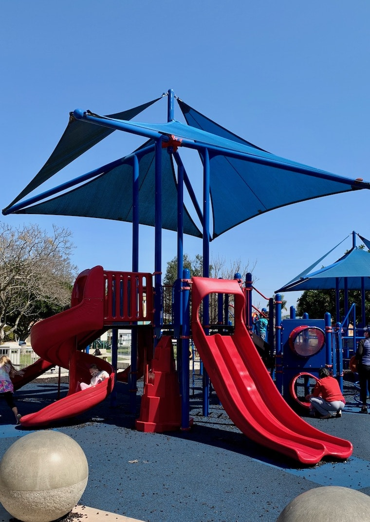 red and blue play structure in Polliwog Park in Manhattan Beach