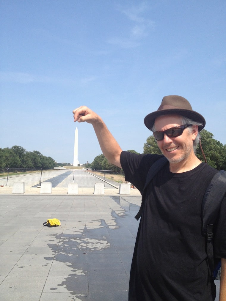 man pretending to touch the top of the washington monument in Washington, D.C. using a camera trick