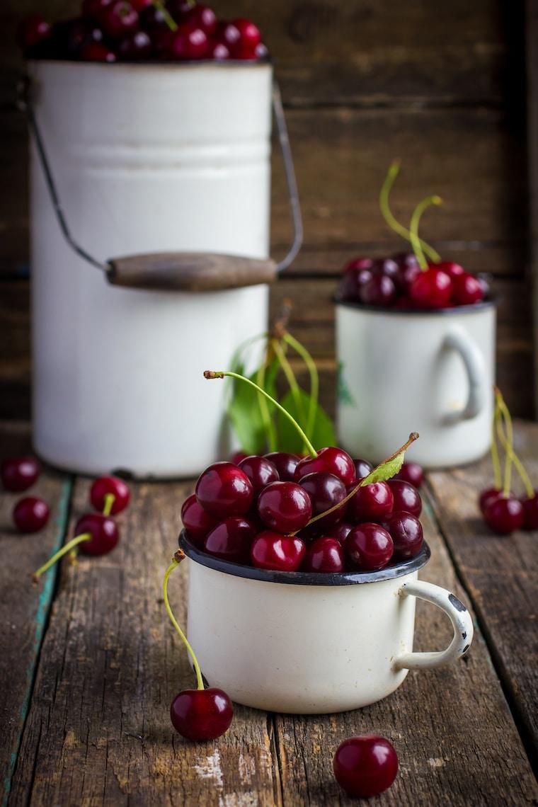 fresh cherries in enamel kitchenware on wooden background