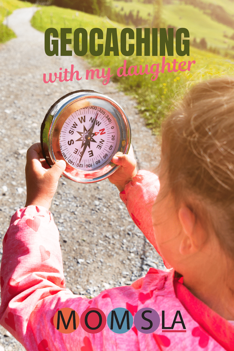 girl holding compass text geocaching with my daughter