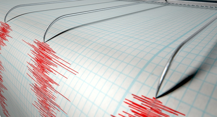 A closeup of a seismograph machine needle drawing a red line on graph paper depicting seismic and earthquake activity