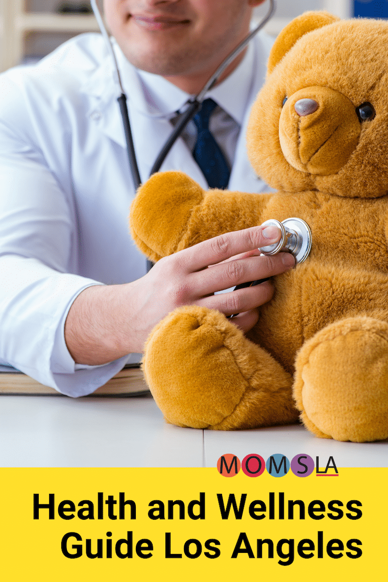 man in white lab coat using stethoscope to listen to teddy bear text health and wellness guide los angeles