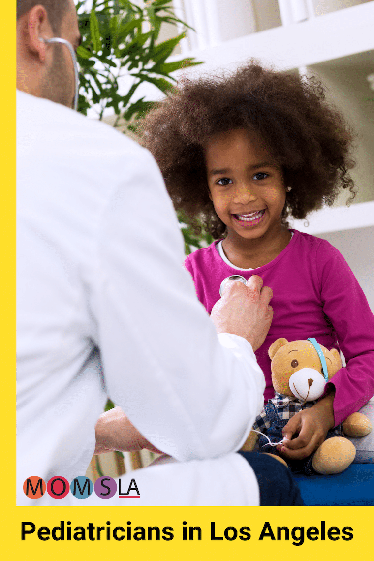 doctor in white lab coat using a stethoscope to listen to the heart of a young Black girl who is smiling at the camera and holding a teddy bear text pediatricians in Los Angeles