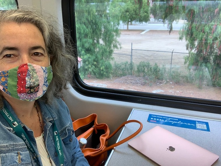 Woman seated at a table by a window on the Metrolink train