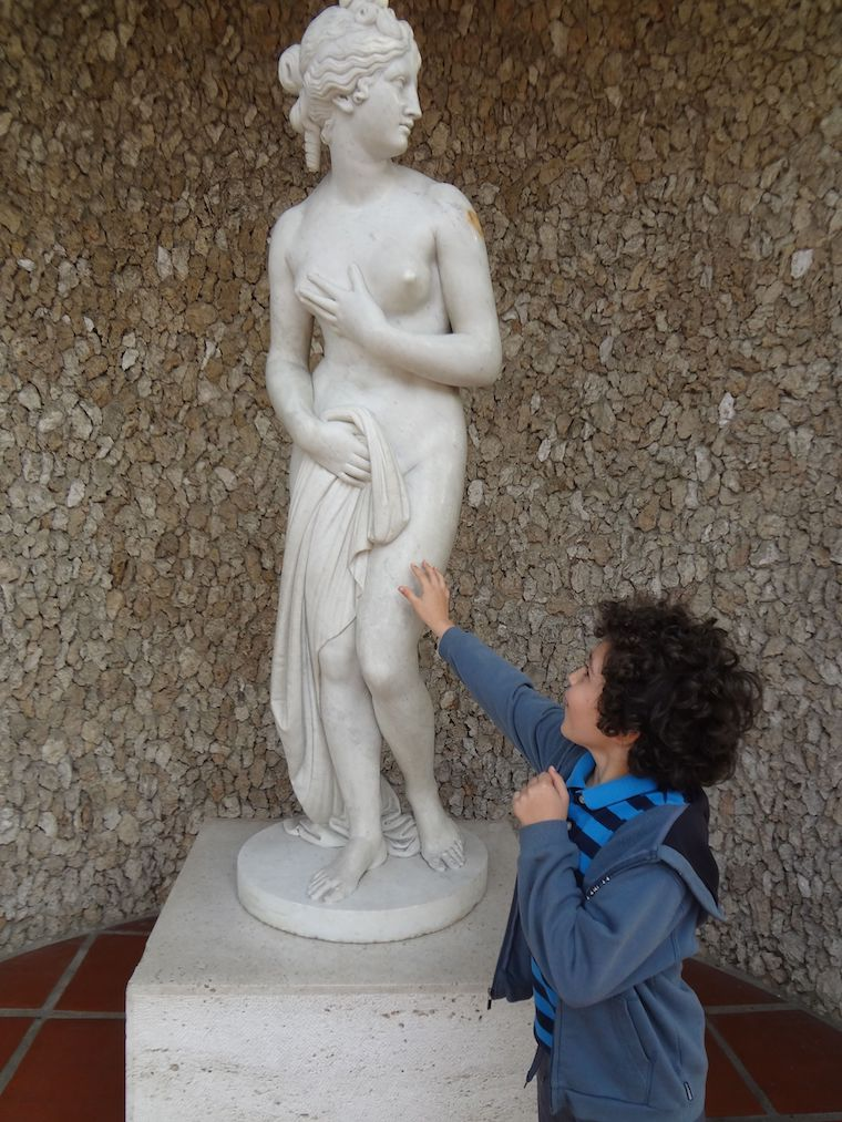 child touching the statue you're allowed to touch at the Getty Villa