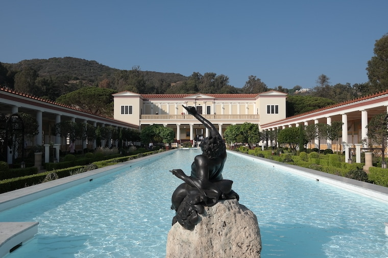 Getty Villa reflecting pond seen from behind the sculpture