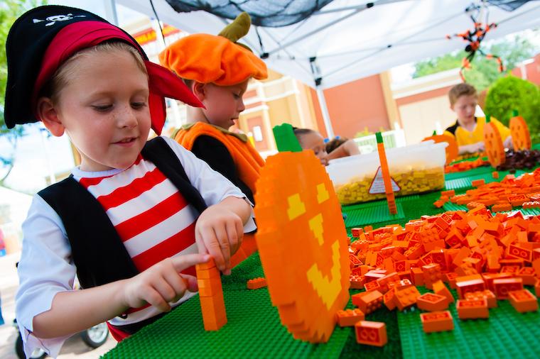 boy in pirate costume making a lego pumpkin at legoland